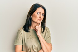 Middle age brunette woman wearing casual clothes smiling looking confident at the camera with crossed arms and hand on chin. thinking positive.