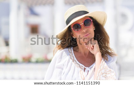 Middle age brunette woman wearing sunglasses and summer hat serious face thinking about question, very confused idea #1141151390