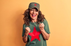 Middle age brunette woman wearing t-shirt and cap with red star symbol of communism celebrating surprised and amazed for success with arms raised and eyes closed