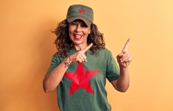 Middle age brunette woman wearing t-shirt and cap with red star symbol of communism smiling and looking at the camera pointing with two hands and fingers to the side.