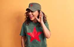 Middle age brunette woman wearing t-shirt and cap with red star symbol of communism smiling with hand over ear listening and hearing to rumor or gossip. Deafness concept.