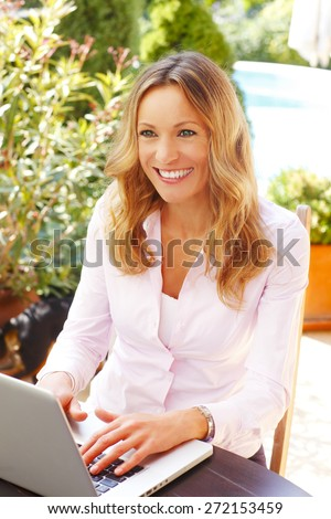 Middle age businesswoman portrait. Attractive mature woman sitting at garden at home and working on laptop while looking at camera and smiling.