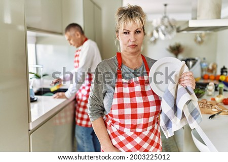 Middle age caucasian couple wearing apron washing dishes at home thinking attitude and sober expression looking self confident  Сток-фото ©