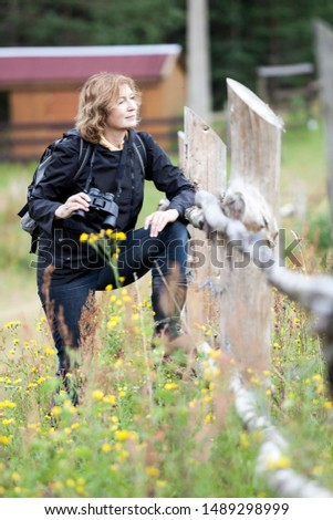 Middle age Caucasian woman bird watcher stands near wooden fence with binoculars for birdwatching as a hobby