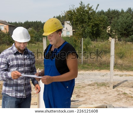 Middle Age Civil Engineer Discussing with Construction Worker About the Project Plans at the Construction Site.