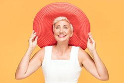 Middle age cool woman wearing red summer hat looking at camera and smiling, posing on yellow studio background.