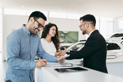 Middle age couple choosing and buying car at car showroom. Car salesman helps them to make right decision.