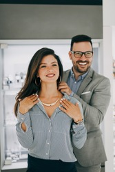 Middle age couple enjoying in shopping at modern jewelry store. Young woman try it out gorgeous necklace and earrings.