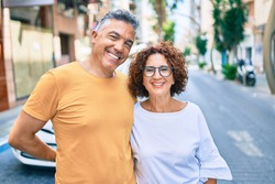 Middle age couple smiling happy standing at street of city.