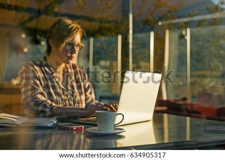 Shutterstock Middle Age Female working on Freelance Project using Portable Computer and making Notes in the Paper Notepad sitting at Table in suburban Cafe throw the Window View focus on Coffee Mug.