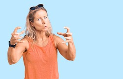 Middle age fit blonde woman wearing casual summer clothes and sunglasses shouting frustrated with rage, hands trying to strangle, yelling mad