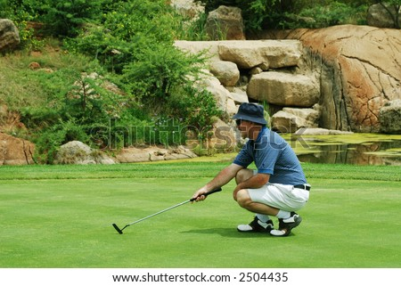 Middle age golfer estimating the line for the putt on South African golf course.