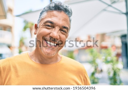 Middle age grey-haired man smiling happy walking at street of city.