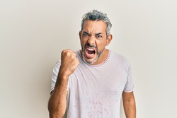 Middle age grey-haired man wearing casual clothes angry and mad raising fist frustrated and furious while shouting with anger. rage and aggressive concept.