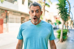 Middle age grey-haired man wearing casual clothes at street of city scared and amazed with open mouth for surprise, disbelief face