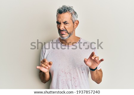 Middle age grey-haired man wearing casual clothes disgusted expression, displeased and fearful doing disgust face because aversion reaction. with hands raised  Foto stock ©