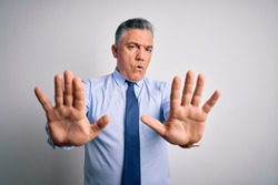 Middle age handsome grey-haired business man wearing elegant shirt and tie Moving away hands palms showing refusal and denial with afraid and disgusting expression. Stop and forbidden.