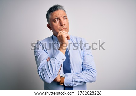 Middle age handsome grey-haired business man wearing elegant shirt and tie with hand on chin thinking about question, pensive expression. Smiling with thoughtful face. Doubt concept.