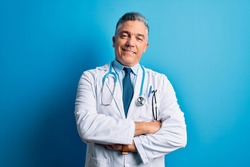 Middle age handsome grey-haired doctor man wearing coat and blue stethoscope happy face smiling with crossed arms looking at the camera. Positive person.