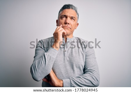 Middle age handsome grey-haired man wearing casual t-shirt over white background with hand on chin thinking about question, pensive expression. Smiling with thoughtful face. Doubt concept.