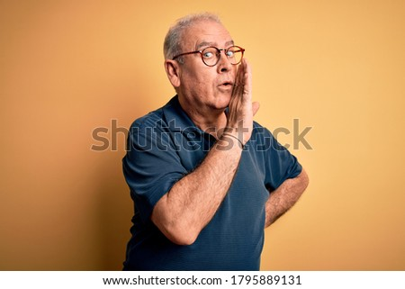 Middle age handsome hoary man wearing casual polo and glasses over yellow background hand on mouth telling secret rumor, whispering malicious talk conversation Photo stock ©