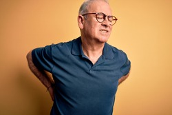 Middle age handsome hoary man wearing casual polo and glasses over yellow background Suffering of backache, touching back with hand, muscular pain