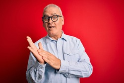 Middle age handsome hoary man wearing casual striped shirt and glasses over red background clapping and applauding happy and joyful, smiling proud hands together