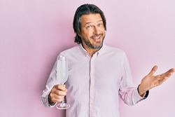 Middle age handsome man drinking a glass of sparkling champagne celebrating achievement with happy smile and winner expression with raised hand