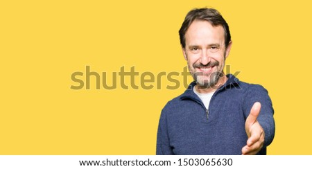 Middle age handsome man wearing a sweater smiling friendly offering handshake as greeting and welcoming. Successful business.