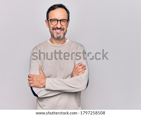 Middle age handsome man wearing casual sweater and glasses over isolated white background happy face smiling with crossed arms looking at the camera. Positive person. Foto stock ©