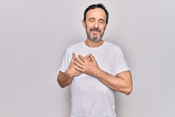 Middle age handsome man wearing casual t-shirt standing over isolated white background smiling with hands on chest, eyes closed with grateful gesture on face. Health concept.