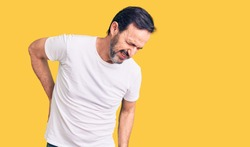 Middle age handsome man wearing casual t-shirt suffering of backache, touching back with hand, muscular pain