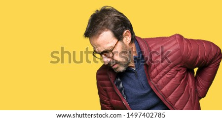 Middle age handsome man wearing glasses and winter coat Suffering of backache, touching back with hand, muscular pain