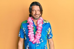 Middle age handsome man wearing summer shirt and hawaiian lei with a happy and cool smile on face. lucky person.