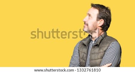 Middle age handsome man wearing winter vest smiling looking to the side with arms crossed convinced and confident