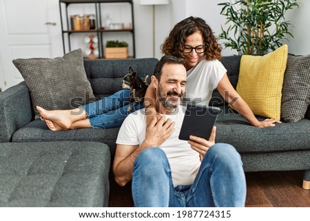 Middle age hispanic couple smiling happy and using touchpad. Sitting on the sofa with dogs at home. Stock fotó ©