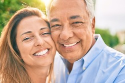 Middle age hispanic couple smiling happy hugging at the promenade.