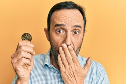 Middle age hispanic man holding virtual currency ethereum coin covering mouth with hand, shocked and afraid for mistake. surprised expression