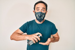Middle age hispanic man wearing covid-19 protection mask using hand sanitizer gel afraid and shocked with surprise and amazed expression, fear and excited face.