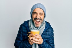 Middle age hispanic man wearing winter scarf and drinking a cup of hot coffee smiling and laughing hard out loud because funny crazy joke.