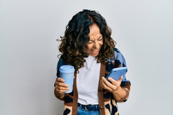 Middle age hispanic woman drinking a cup of coffee and looking at the smartphone screen smiling and laughing hard out loud because funny crazy joke.