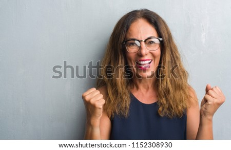 Middle age hispanic woman over grey wall wearing glasses screaming proud and celebrating victory and success very excited, cheering emotion