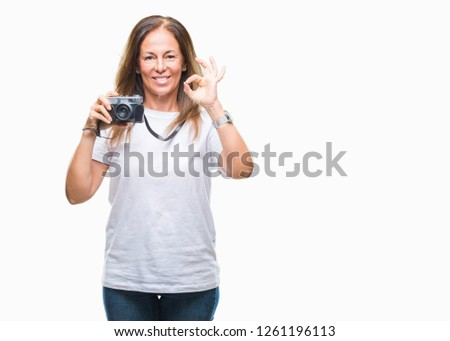 Middle age hispanic woman taking pictures using vintage photo camera over isolated background doing ok sign with fingers, excellent symbol