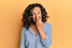 Middle age hispanic woman wearing casual clothes looking stressed and nervous with hands on mouth biting nails. anxiety problem.