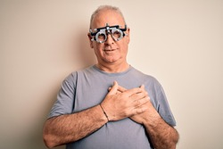 Middle age hoary man controlling vision wearing optometry glasses over white background smiling with hands on chest with closed eyes and grateful gesture on face. Health concept.