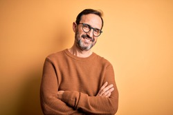 Middle age hoary man wearing brown sweater and glasses over isolated yellow background happy face smiling with crossed arms looking at the camera. Positive person.