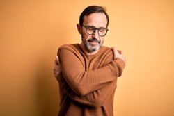 Middle age hoary man wearing brown sweater and glasses over isolated yellow background Hugging oneself happy and positive, smiling confident. Self love and self care