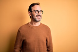 Middle age hoary man wearing brown sweater and glasses over isolated yellow background looking away to side with smile on face, natural expression. Laughing confident.