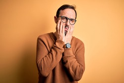 Middle age hoary man wearing brown sweater and glasses over isolated yellow background Tired hands covering face, depression and sadness, upset and irritated for problem