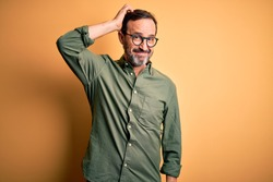 Middle age hoary man wearing casual green shirt and glasses over isolated yellow background confuse and wonder about question. Uncertain with doubt, thinking with hand on head. Pensive concept.